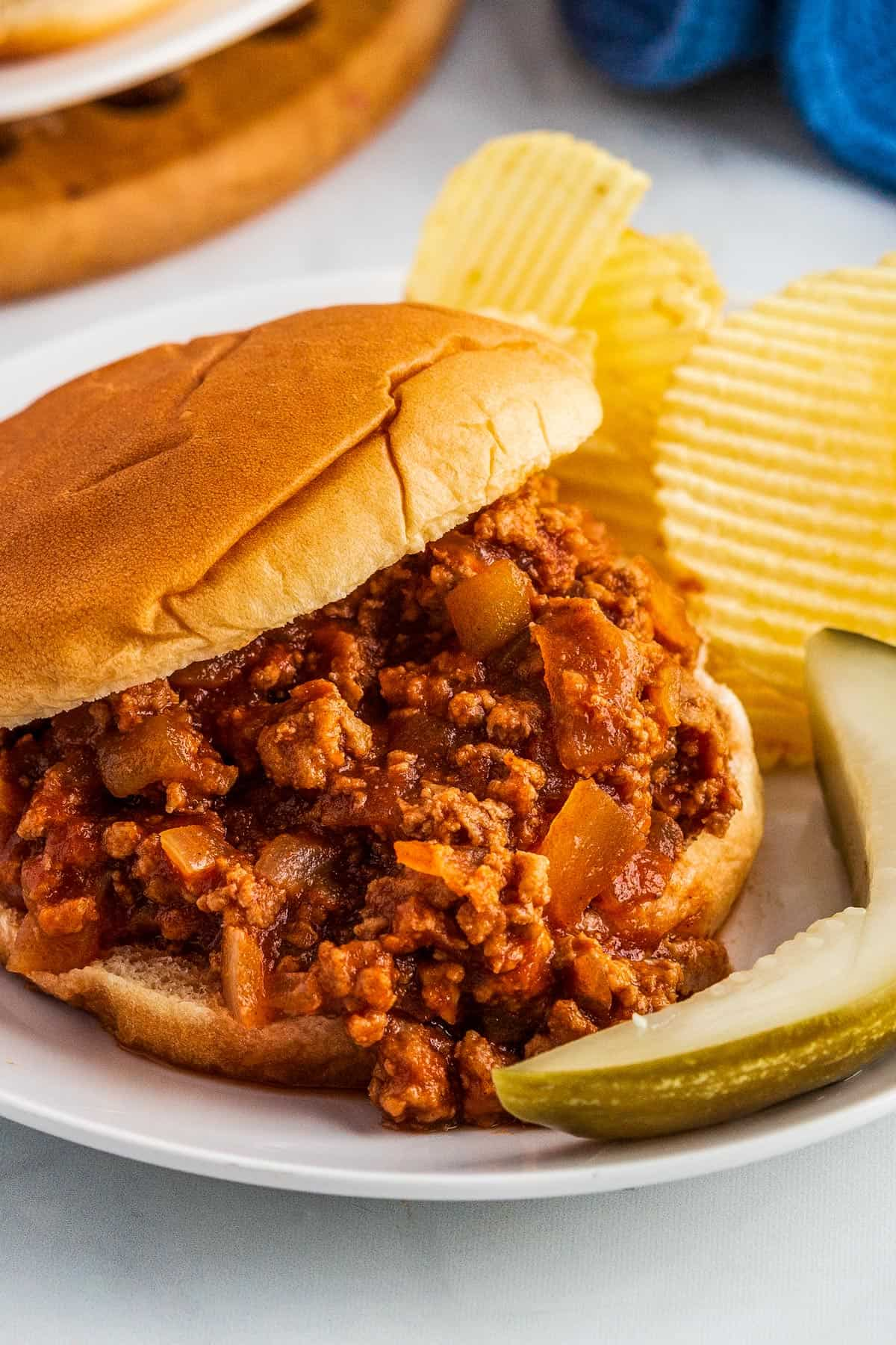 Sloppy Joe on a white plate with pickles and potato chips